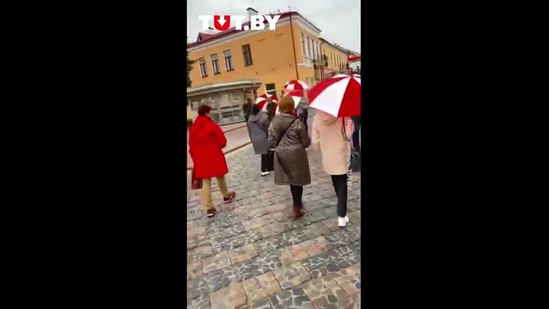 Женщины с красно белыми зонтами в Гродно днем 24 октября