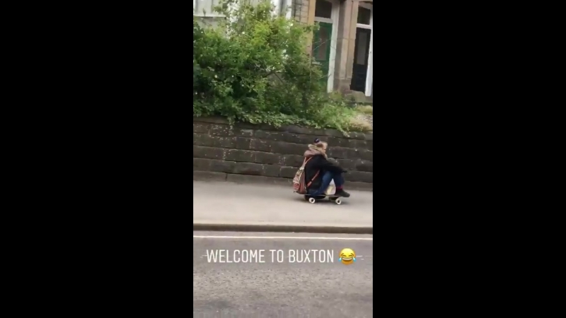 Random women walks dog downhill as she sits on the skateboard